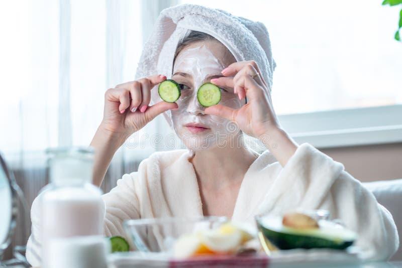 Красивая молодая женщина с естественными косметическими кусками маски и огурца на ее стороне Забота и процедуры спа кожи дома стоковая фотография rf
