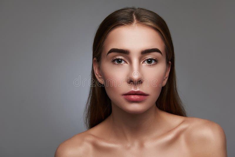 Красивая молодая женщина с естественным макияжем представляя против серой предпосылки стоковые фотографии rf
