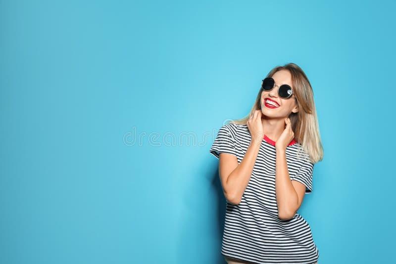 Красивая молодая женщина с здоровыми длинными белокурыми волосами на предпосылке цвета стоковое фото