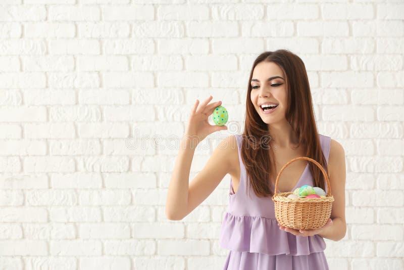 Красивая молодая женщина с корзиной вполне красочных пасхальных яя против белой кирпичной стены стоковые изображения