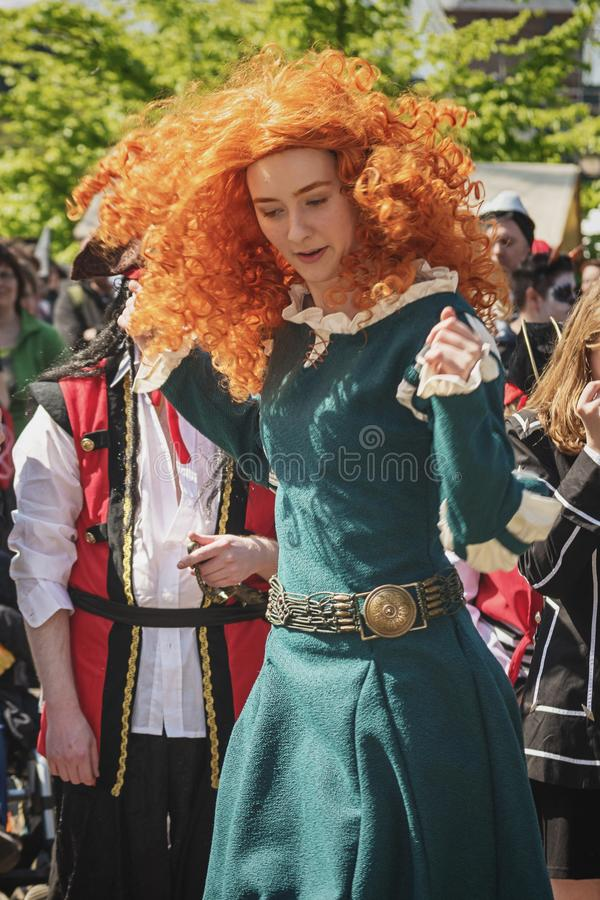 Красивая молодая женщина с красным париком танцует во время вентилятора эльфа стоковое изображение rf