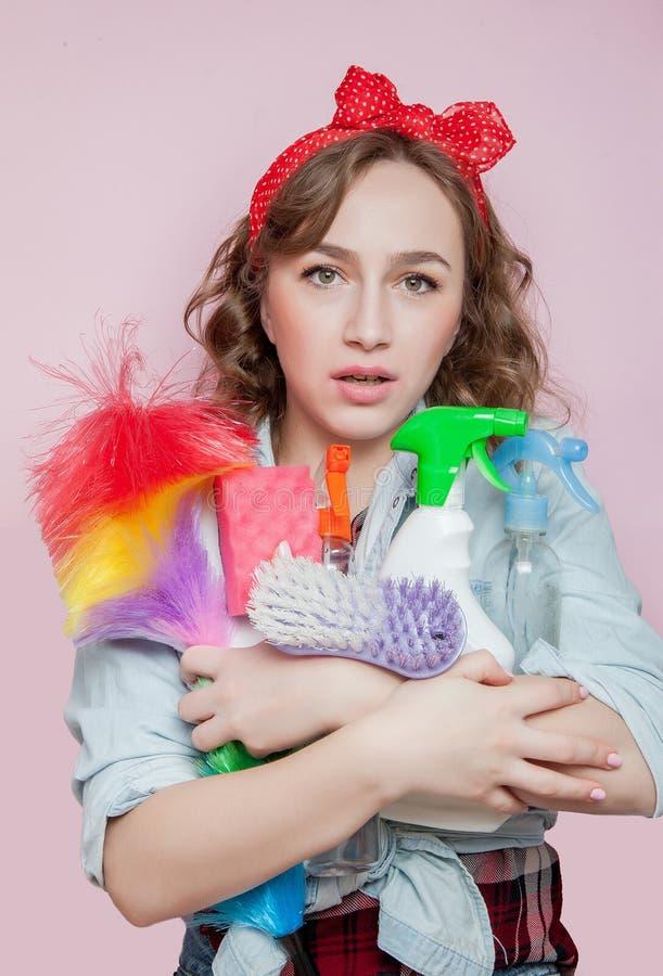 Красивая молодая женщина с макияжем штыря-вверх и стиль причесок с очищая инструментами на розовой предпосылке стоковое изображение rf