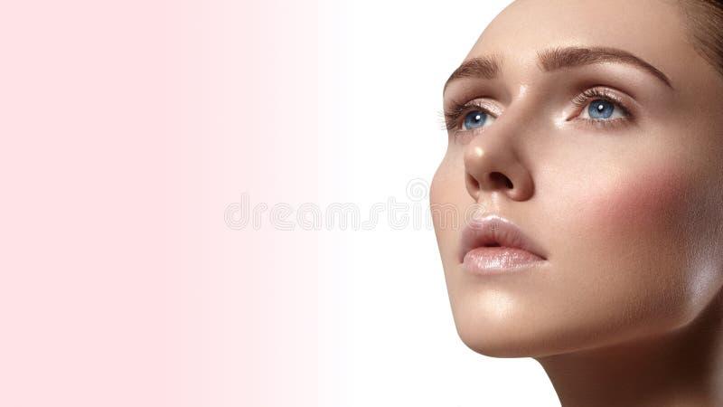 Красивая молодая женщина с совершенной чистой сияющей кожей, естественным составом моды Женщина конца-вверх, взгляд курорта красо стоковая фотография