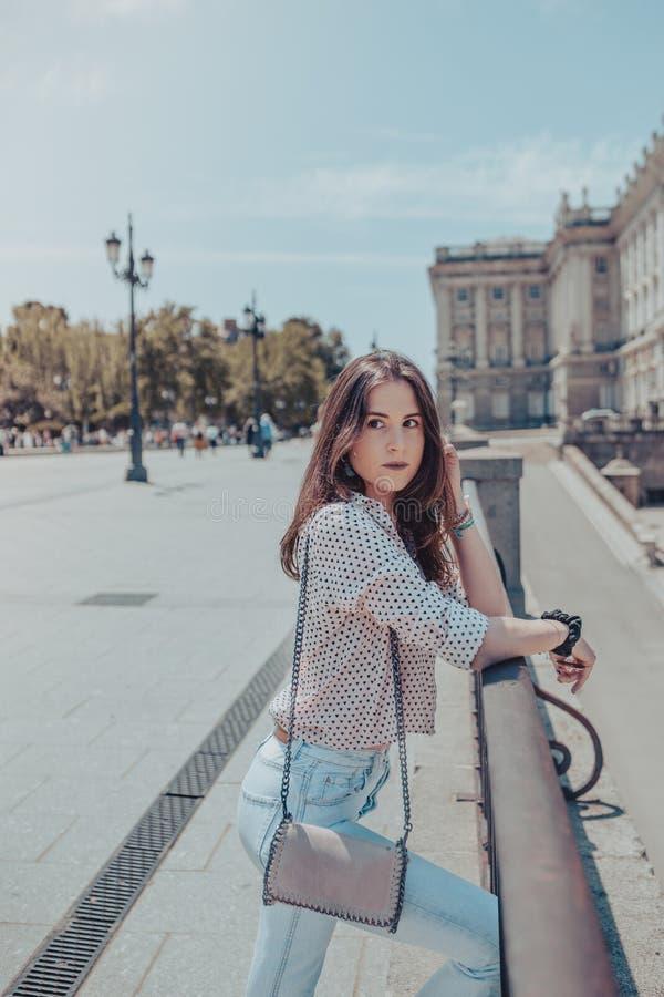 Красивая молодая женщина с сумкой отдыхая на перилах около королевского дворца Мадрида, Испании стоковые изображения
