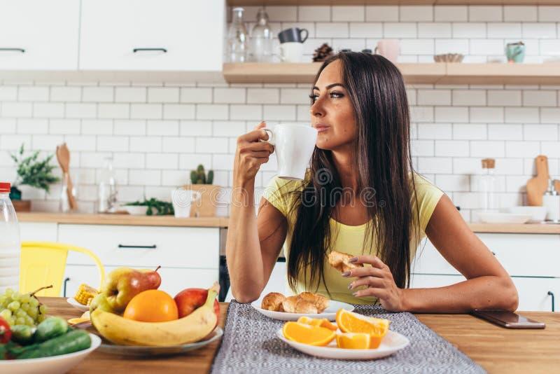 Красивая молодая женщина с чашкой кофе дома против предпосылки кухни стоковые фотографии rf