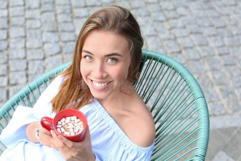 Красивая молодая женщина с чашкой сладкого напитка какао в кафе outdoors стоковые изображения