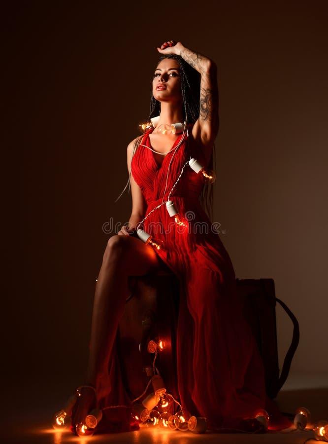 Красивая молодая женщина с dreadlocks и ретро строкой освещает на праздник рождества стоковое изображение