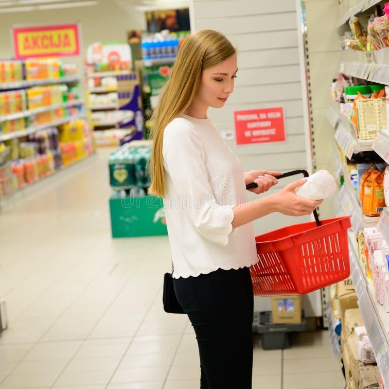 Красивая молодая женщина ходя по магазинам в гастрономе, принимая еду полки стоковые изображения rf