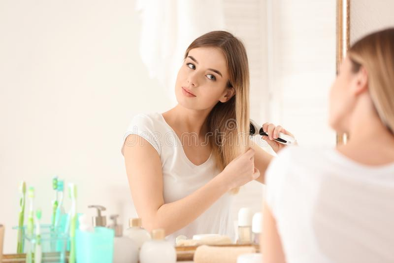 Красивая молодая женщина чистя ее волосы щеткой в утре стоковые фотографии rf