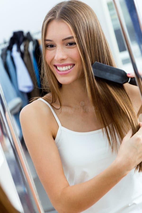 Красивая молодая женщина чистя ее длинные волосы щеткой перед ее зеркалом стоковое изображение