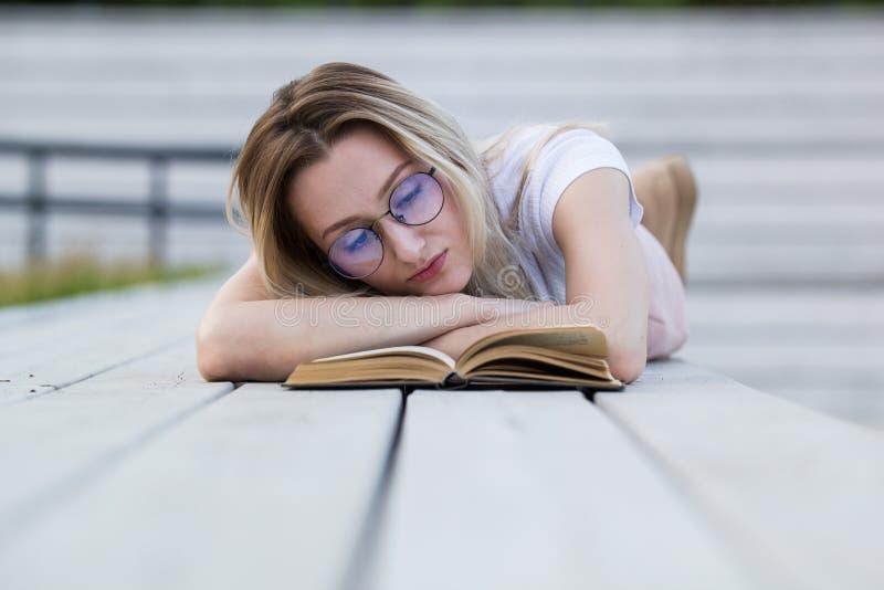 Красивая молодая женщина читая книгу лежа на стенде в парке стоковое изображение