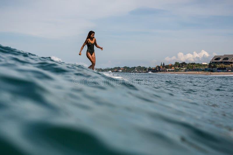 Красивая молодая индонезийская женщина в волне бикини занимаясь серфингом в Бали на предпосылке голубого неба, облаков и тропичес стоковое изображение rf