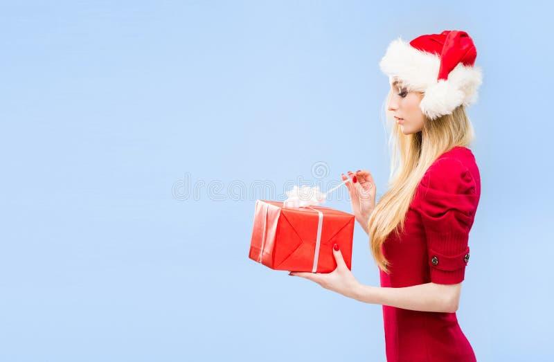 Красивая, молодая и милая девушка в шляпе рождества над предпосылкой с снегом стоковые фотографии rf