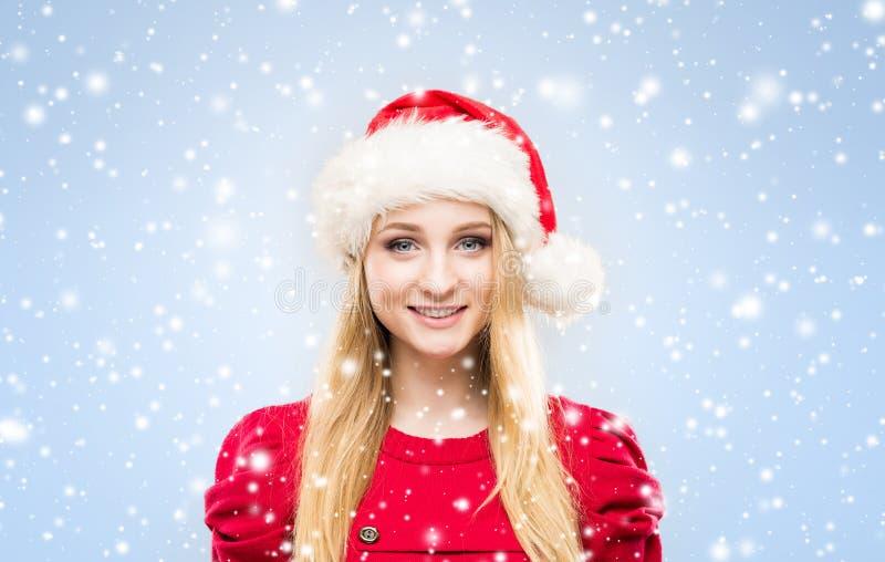 Красивая, молодая и милая девушка в шляпе рождества над предпосылкой с снегом стоковые фото