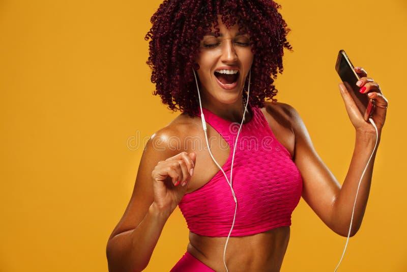 Красивая молодая и подходящая женщина в музыке наушников слушая от телефона и усмехаться Изолированный на желтой предпосылке в ро стоковые изображения rf
