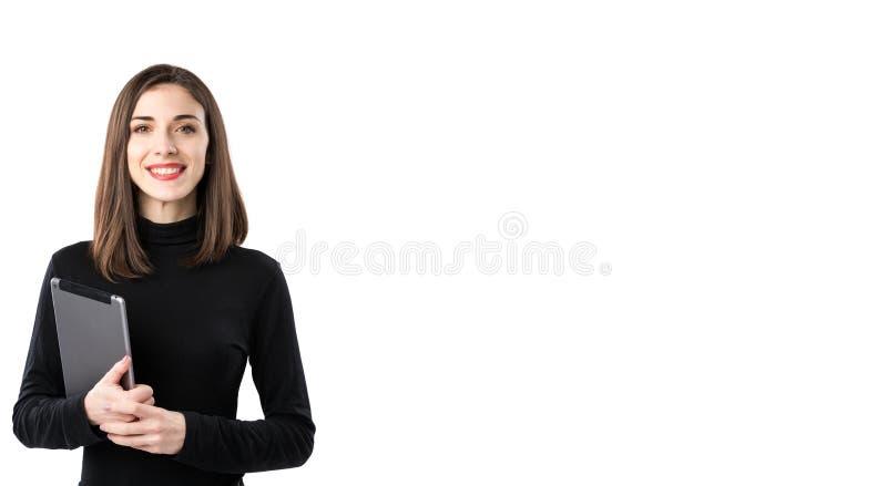E Красивая молодая кавказская женщина в черной рубашке представляя положение с руками планшета дальше стоковые фото