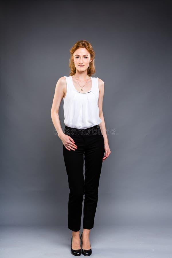 Красивая молодая кавказская женщина с длинными красными волосами в высоких пятках, черных брюках и белой рубашке стоит полностью  стоковое изображение