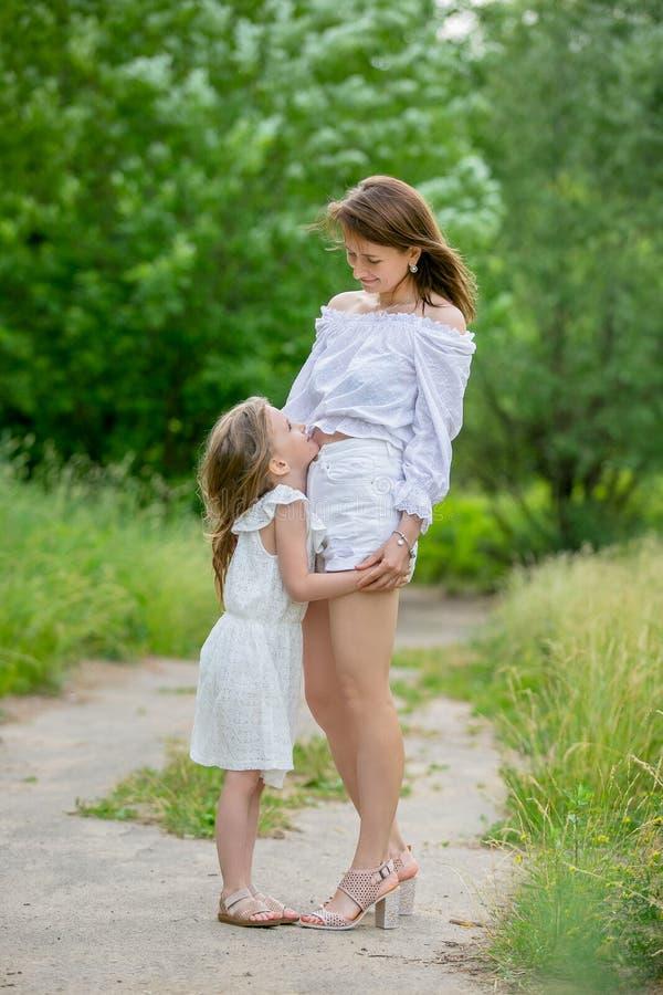 Красивая молодая мать и ее маленькая дочь в белом платье имея потеху в пикнике Они стоят на дороге в парке, объятии и стоковое фото rf
