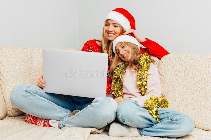 Красивая молодая мать и ее маленькая дочь одетые в Санта стоковое изображение