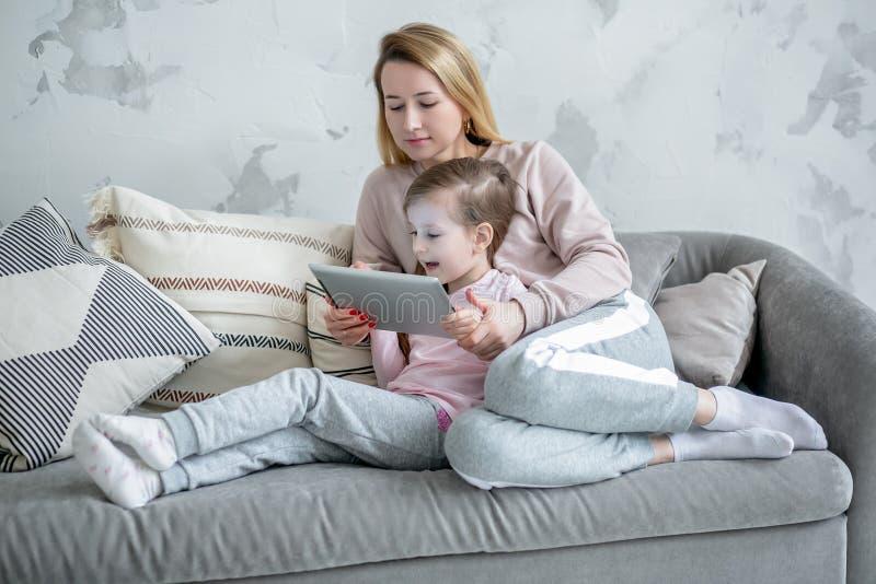 Красивая молодая мать и ее маленькие фильмы дозора дочери совместно, игра на планшете и радоваться сидеть на софе Объятия мамы стоковое изображение