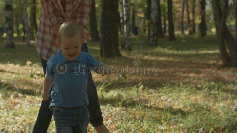 Красивая молодая мать и ее прелестный сын малыша имея потеху совместно в парке осени, мальчике бегут от его мамы стоковая фотография rf