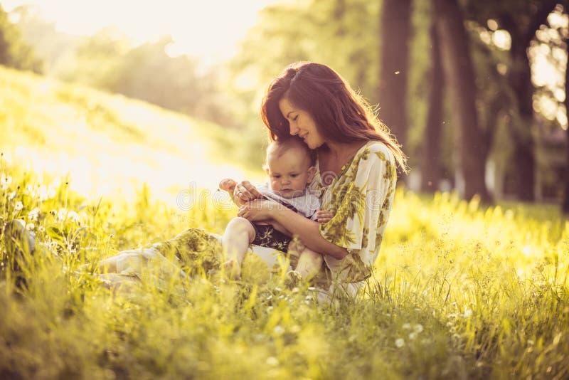 Красивая молодая мать с ее сыном младенца на природе Портрет стоковые фото