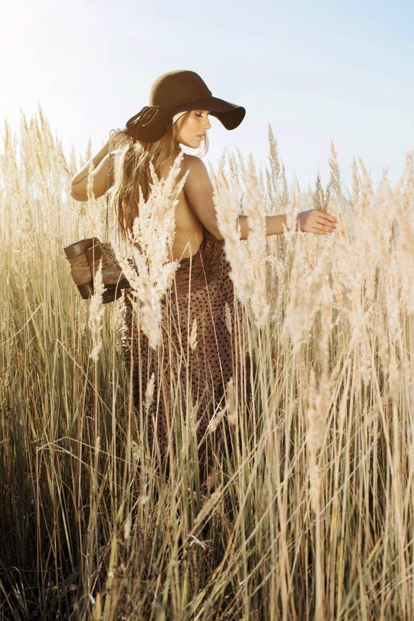 Красивая молодая модель идя через tallgrass на золотом часе стоковое фото rf