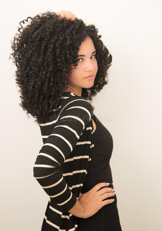 Красивая молодая модель представляя с большим черным вьющиеся волосы стоковая фотография rf