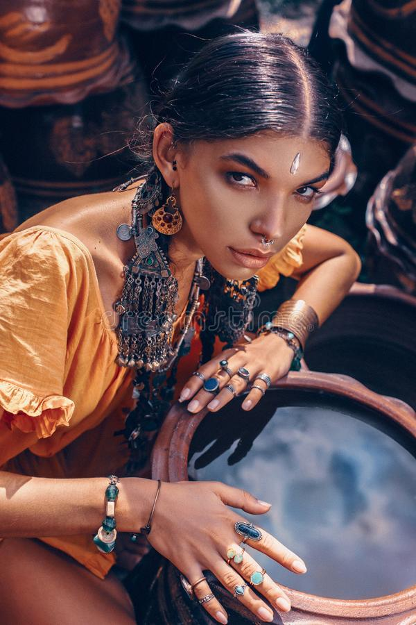 Красивая молодая модная женщина с составляет и стильные аксессуары boho представляя на естественной тропической предпосылке стоковое изображение