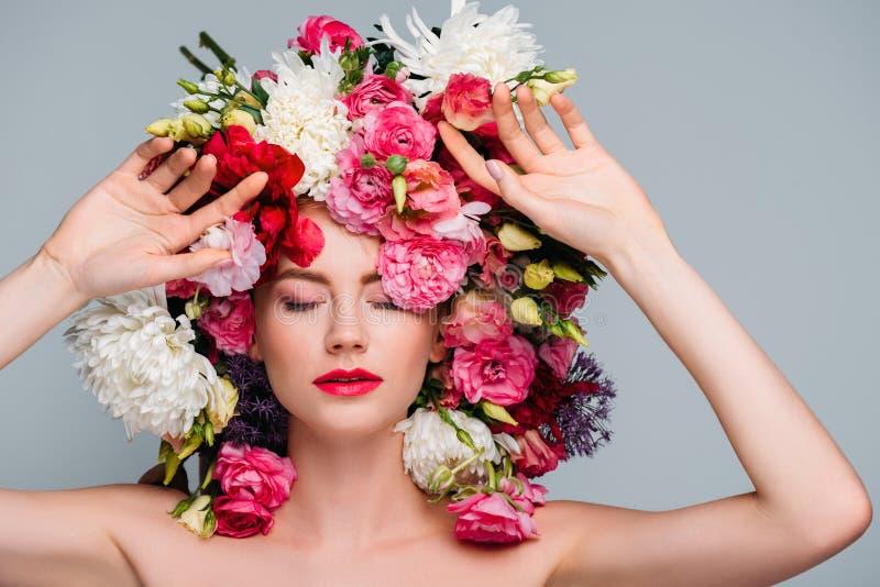 красивая молодая нагая женщина с закрытыми глазами представляя с цветками на голове стоковое фото