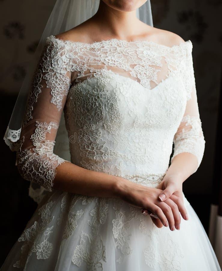 Красивая молодая невеста в белом ожидании платья холит внутри помещения Элегантная очаровательная молодая невеста брюнета предста стоковое фото rf
