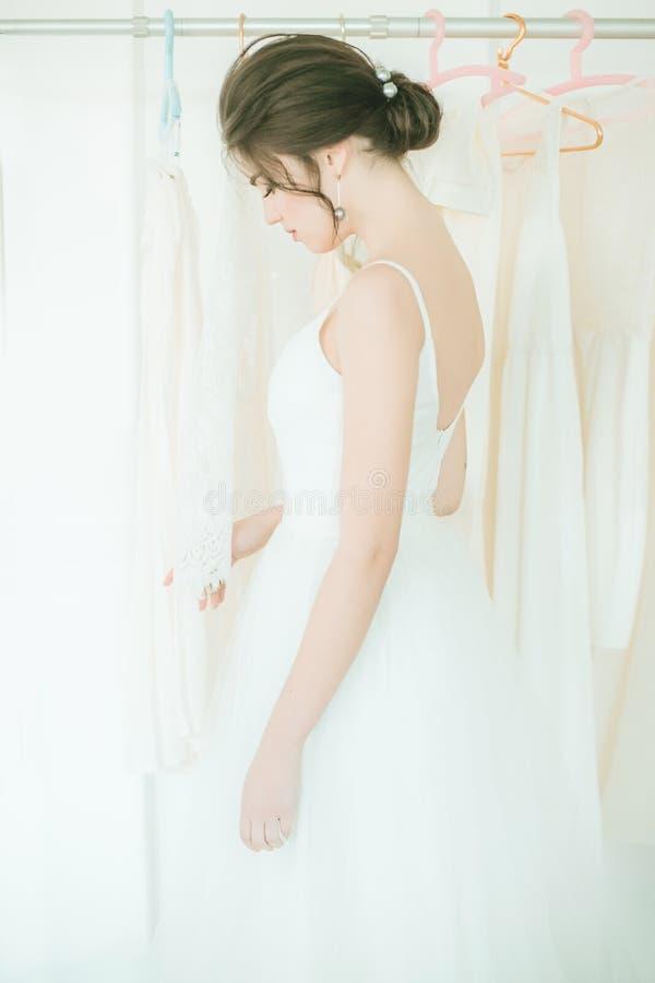 Красивая молодая невеста в белом платье в салоне на предпосылке других платьев стоковые изображения rf