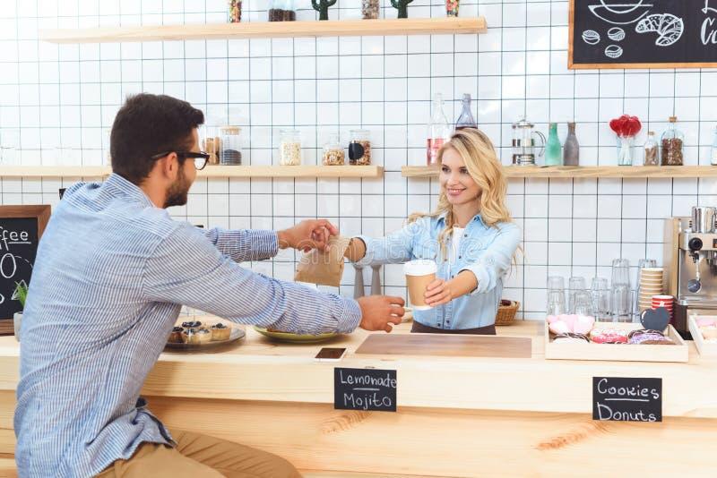 красивая молодая официантка давая бумажный стаканчик и взятие отсутствующая еда к клиенту стоковые фото
