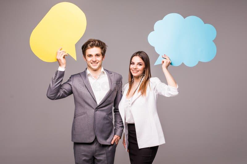 Красивая молодая пара держит пузыри речи, смотрит камеру и усмехается, на сером цвете стоковые изображения rf