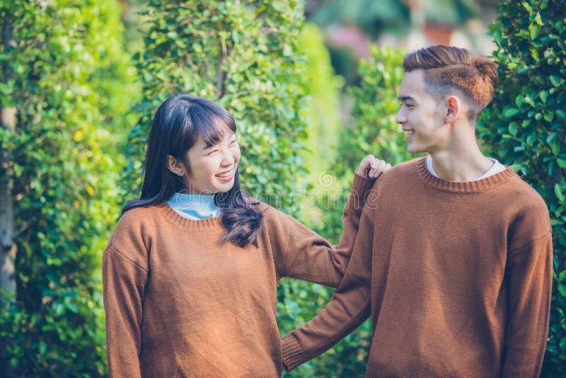 Красивая молодая пара смотрит усмехаться счастливый в влюбленности outdoors стоковые фотографии rf