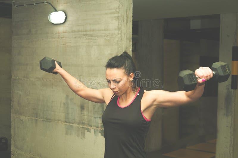 Красивая молодая привлекательная гантель девушки утяжеляет разминку для мышц плеча, реальных людей не тренируя никакой представля стоковая фотография rf