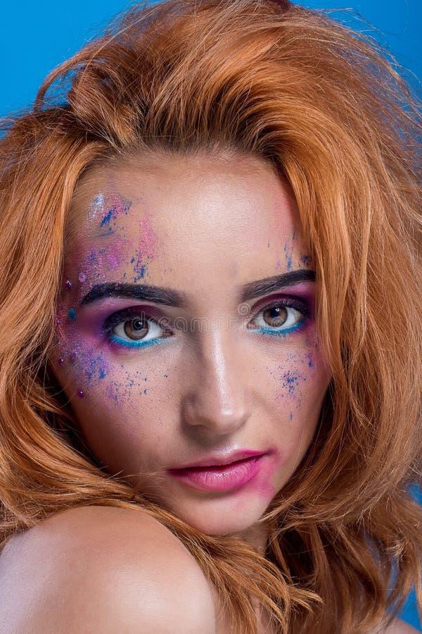 Красивая молодая рыжеволосая девушка с брызгом краски на ее стороне стоковые фото