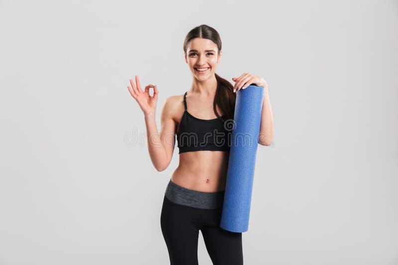 Красивая молодая спортсменка держа циновку йоги и показывая ОДОБРЕННЫЙ знак стоковое изображение rf
