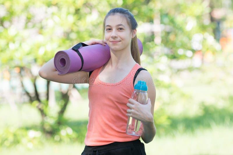 Красивая молодая спортсменка держит бутылку воды и Yog стоковые изображения rf