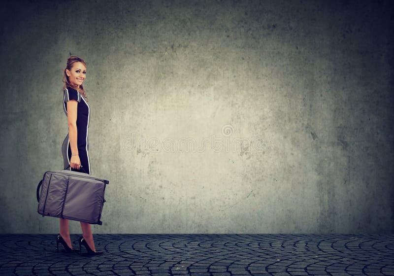 Красивая молодая счастливая женщина с чемоданом готовым для того чтобы путешествовать стоковые изображения