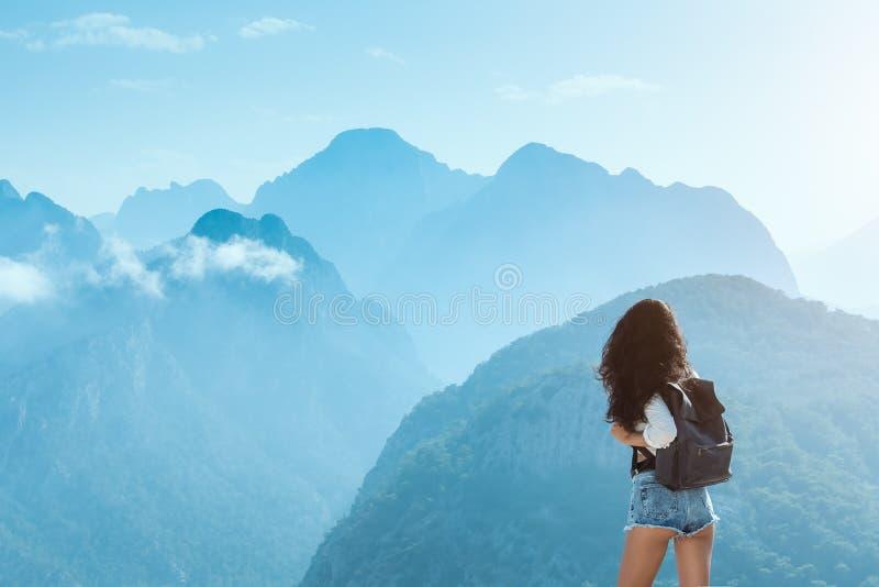 Красивая молодая туристская девушка с рюкзаком на горах стоковая фотография rf