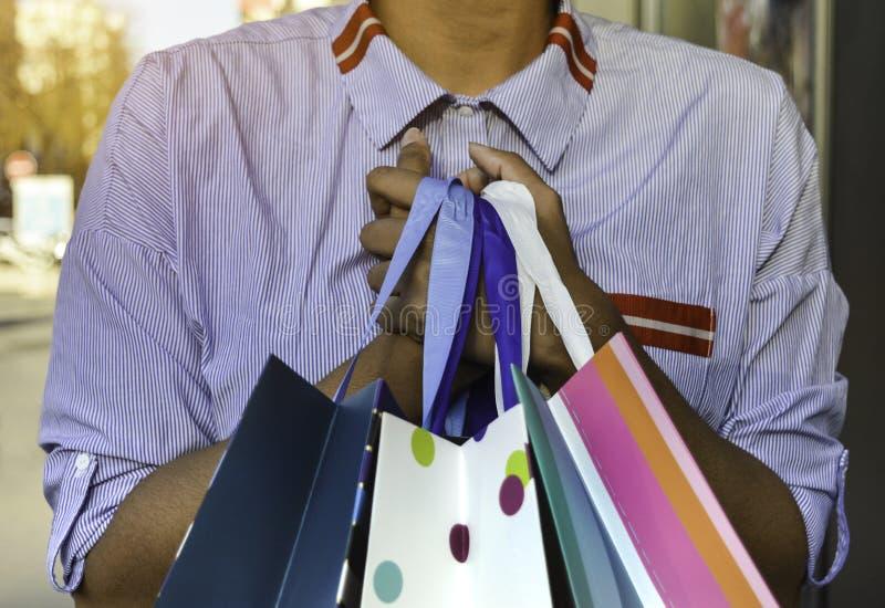 Красивая молодая чернокожая женщина держа хозяйственные сумки Концепция о покупках, образе жизни и людях стоковая фотография