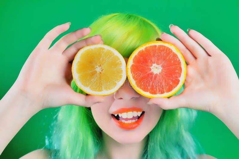 Красивая модельная девушка с красочным стилем причёсок принимает красный и желтый сок на зеленой предпосылке стоковое изображение rf
