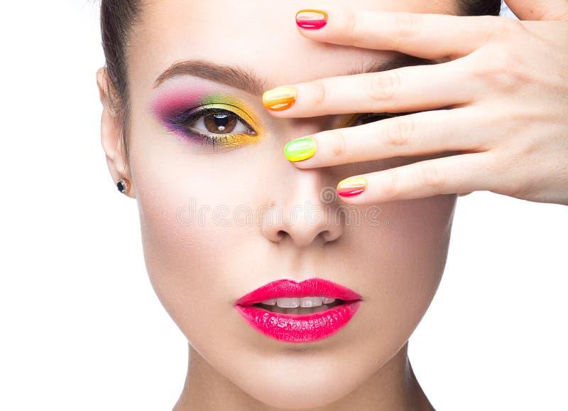 Красивая модельная девушка с ярким покрашенным составом и маникюр в лете отображают Сторона красотки Ногти покрашенные краткостью стоковое изображение