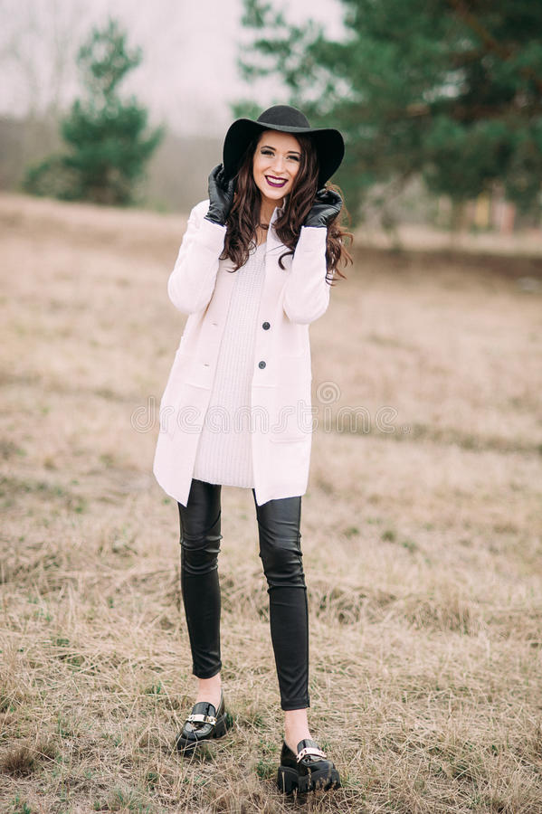 Красивая модная женщина в черной шляпе и белом outdoo пальто стоковое изображение