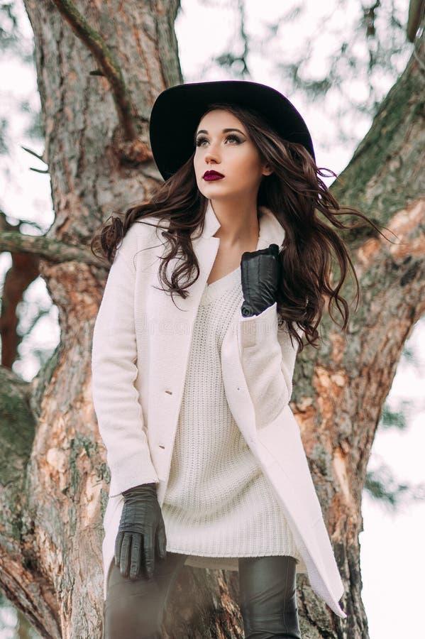 Красивая модная женщина в черной шляпе и белом outdoo пальто стоковые изображения
