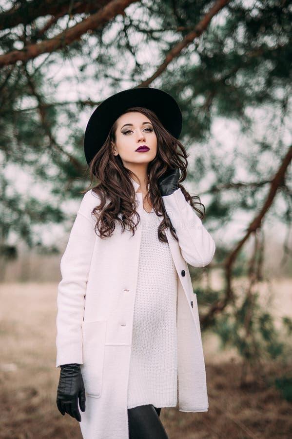 Красивая модная женщина в черной шляпе и белом outdoo пальто стоковая фотография