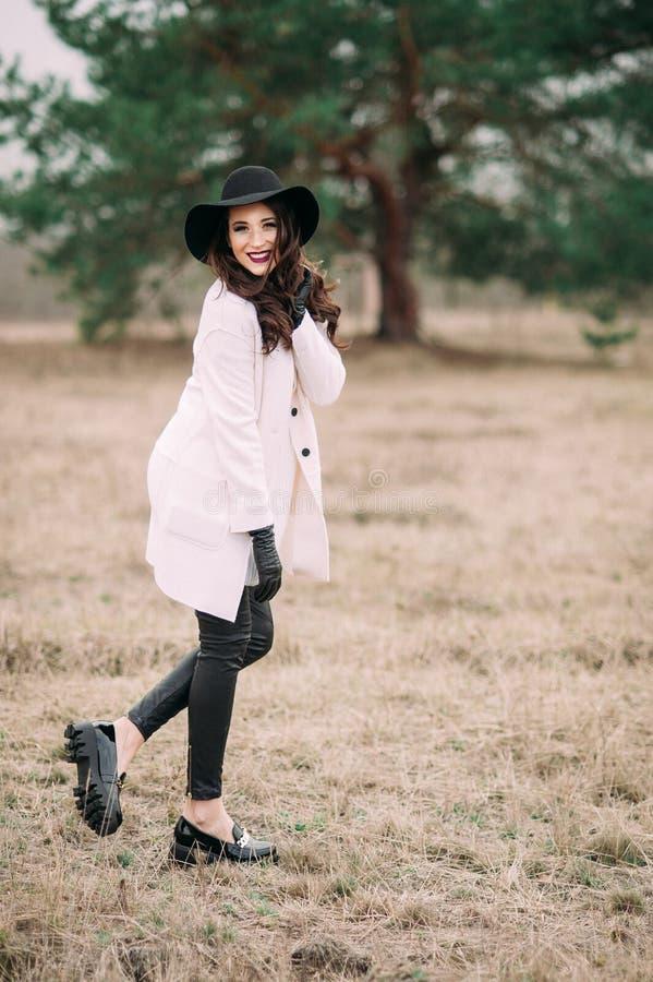 Красивая модная женщина в черной шляпе и белом outdoo пальто стоковое фото rf