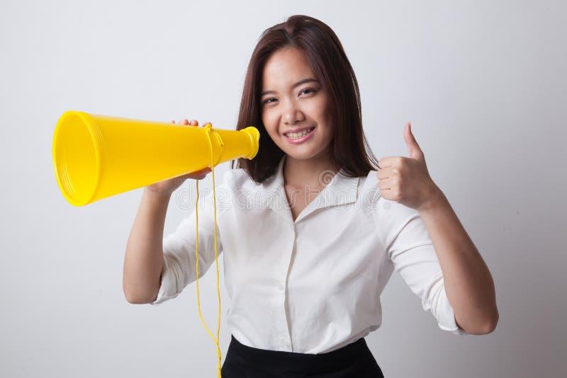 Красивая молодая азиатская выставка женщины thumbs вверх объявляет с megapho стоковая фотография rf
