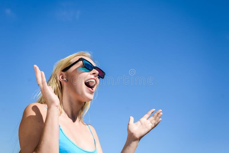 Красивая молодая дама смотря кино с стеклами 3D, голубую светлую предпосылку стоковая фотография